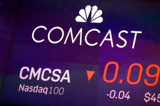 In this Oct. 1, 2019, file photo the symbol for Comcast appears on a screen at the Nasdaq MarketSite, in New York.