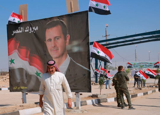 """FILE - In this Sept. 30, 2019, file photo, a man passes a poster of Syrian President Bashar Assad with Arabic that reads, """"Congratulations victory,"""" while crossing the border into Syria at the newly opened crossing between the Iraqi town of Qaim and Syria's Boukamal, Syria."""