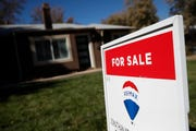 A sign stands outside a home for sale in southeast Denver.