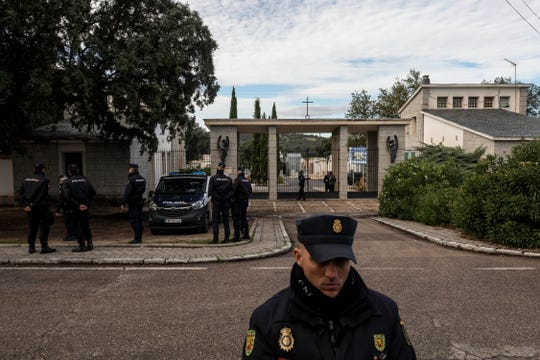 National police officers stand guard at the main gate outside Mingorrubio's cemetery.