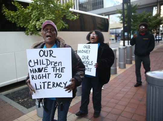 Rosetta Young of Detroit carries a sign insisting that Detroit school children have a right to literacy while protesting outside the Potter Stewart U.S. Federal Courthouse in Cincinnati Thursday morning.