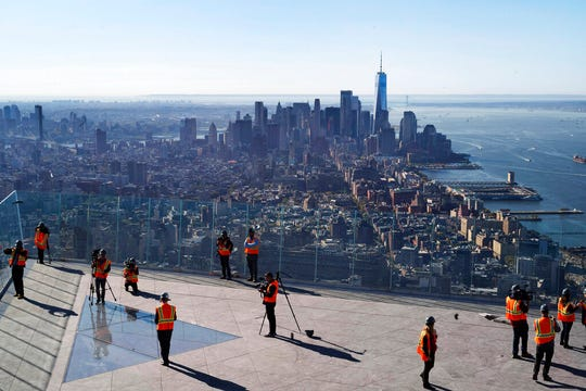 "People walk around ""Edge,"" an outdoor observation deck overlooking New York, during a media tour, Thursday, Oct. 24, 2019."