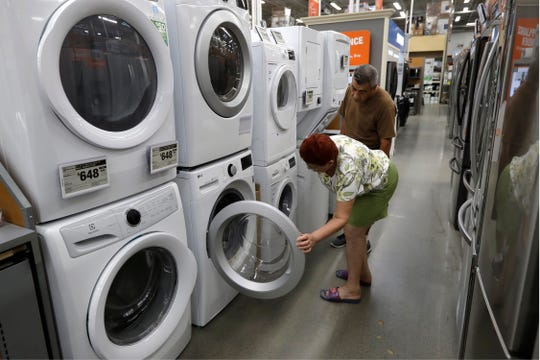 Maria Alvarez, front, and her husband Guillermo Alvarez, behind, both of Boston, examine clothes washers and dryers at a Home Depot in Boston.