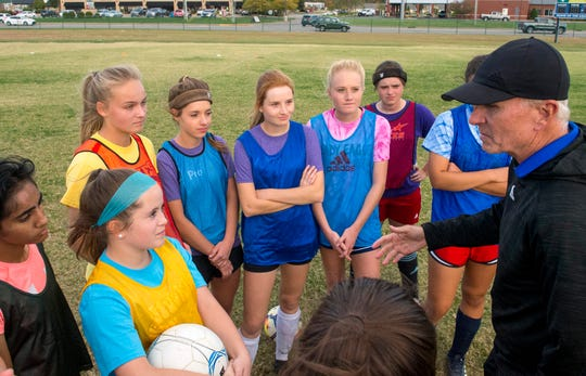 The Goebel sisters, middle from left, Lauren, Danielle, Cassidy, and Sierra listen to Head Coach Tom Dragon in a huddle during practice at Evansville Day School Wednesday evening, Oct. 23, 2019. The Goebel's are quadruplets that play soccer for Evansville Day School who recently won the first regional title in program history.