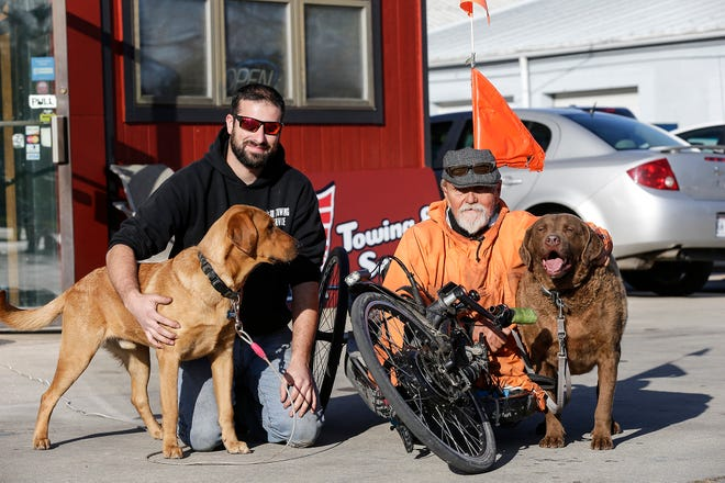 Brandon Hau and his dog Brewtis pose with Floyd Freiberg and his dog OJ Wednesday, Oct. 23, 2019, in Fond du Lac, Wis. Brandon helped Floyd get his modified bike off railroad tracks on Scott Street in Fond du Lac seconds before a train crossed the busy intersection.