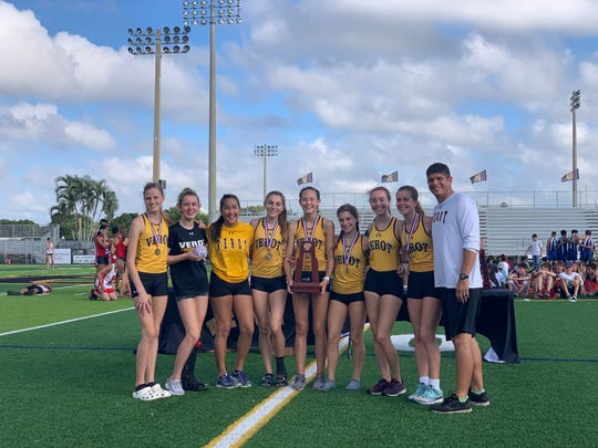 The Bishop Verot girls cross country team poses for pictures with the district trophy following their win in 2A-6.