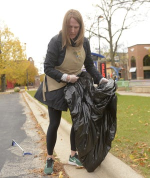 Dana Kressig, a corporate sales executive for the Green Bay Packers, picks up trash in the Broadway district in downtown Green Bay of Oct. 24, 2019.