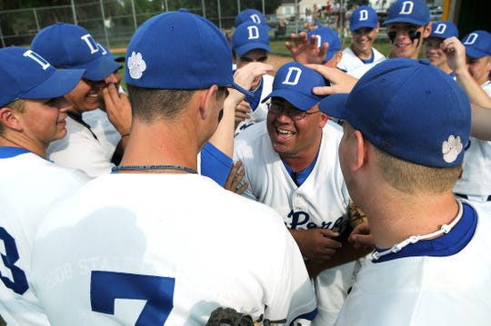 De Pere Legion players pat the head of manager Dan Lukes, right center, before a game in 2009.
