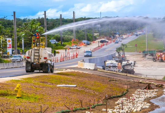 A Black Construction Company employee uses a water cannon atop a water tanker truck to water sprouting grass and to mitigate dust issues along Route 3 in Dededo, near the site of the new Marine base, in this Oct. 24, 2019, file photo.