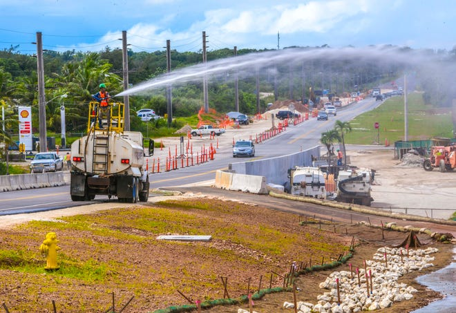 A Black Construction Company employee uses a water cannon atop a water tanker truck to water sprouting grass and to mitigate dust issues as road and shoulder work continues along Route 3 in Dededo, on Thursday, Oct. 24, 2019.