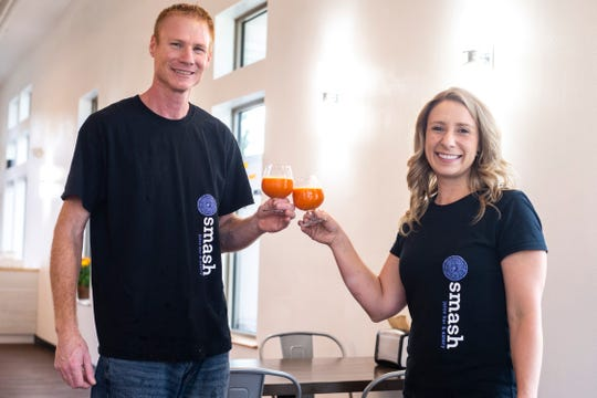 Brandon Crane and Tina Whitney pose for a photo with glasses of Healthy Hippy orange juice, Wednesday, Oct., 23, 2019, at Smash Juice Bar in North Liberty, Iowa.
