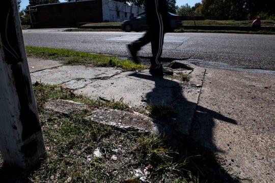 Pedestrian walks on Airway Boulevard with cracks and overgrown grass on the sidewalk.