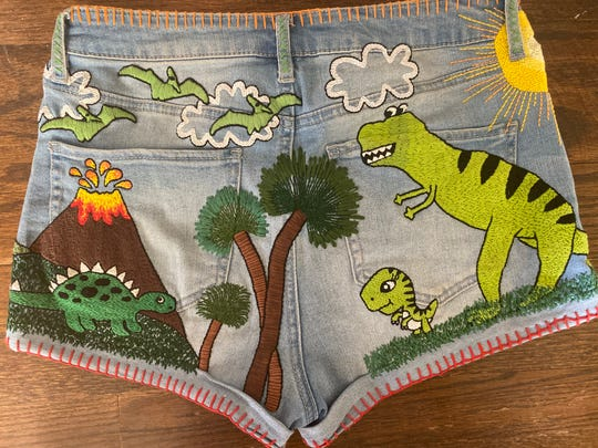 The first project Wallis Woodward created after she took up embroidering as an adult was the dinosaur scene on this thrifted pair of shorts.