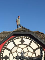 Lorne Koehler-Marsh stands on top of the clock that once sat atop the Hour Time Restaurant in Lafayette. Koehler-Marsh recently bought the clock, which had been in storage since it was auctioned when the restaurant closed in 2016. He plans to move it five miles to Dayton, where he hopes to put it on top of a tower leading to a future clock workshop.