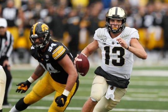 Purdue quarterback Jack Plummer (13) runs from Iowa defensive end A.J. Epenesa, left, during the second half of an NCAA college football game, Saturday, Oct. 19, 2019, in Iowa City, Iowa. Iowa won 26-20. (AP Photo/Charlie Neibergall)