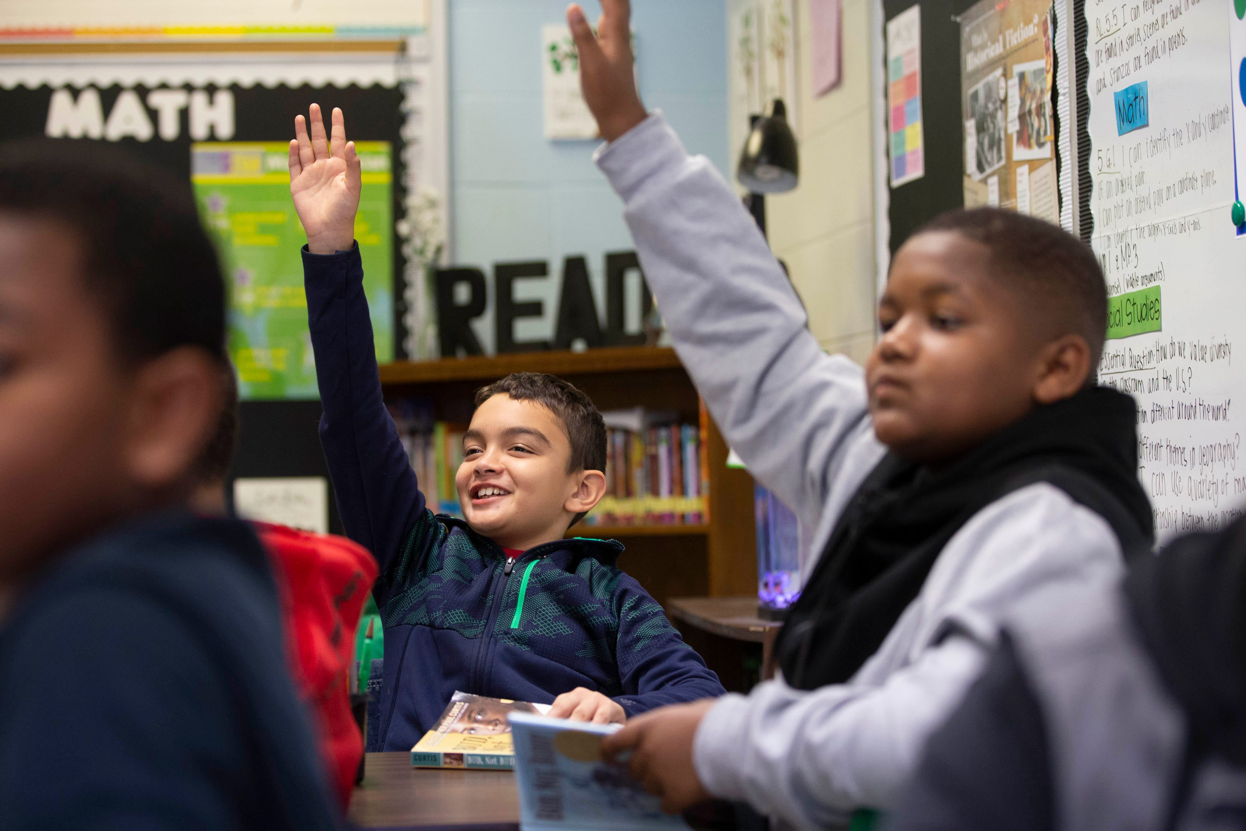Students at Cochran Elementary School, located near the University of Louisville, raise their hands during a reading lesson. Oct. 18, 2019