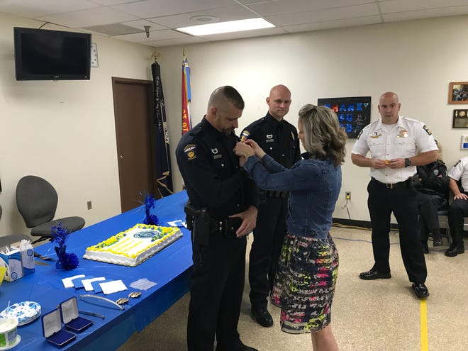 Mansfield police Officer Michael J. Haines' wife pins on a new badge as he is promoted to sergeant Thursday. Officer Ryan C. Grimshaw was promoted to the rank of sergeant. Mansfield police Chief Keith Porch is at right.