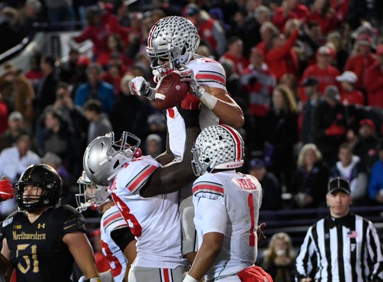 Ohio State wide receiver Austin Mack is lifted in the air by tackle Nicholas Petit-Frere after scoring a touchdown against Northwestern.