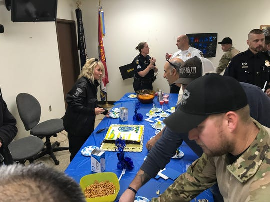Kim Vandayburg, at left, parking control officer at Mansfield Police Department, serves cake at the promotional ceremony Thursday.
