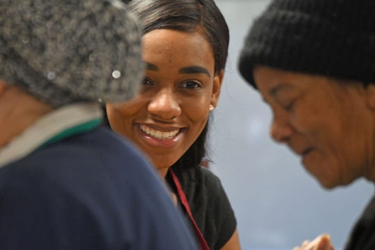 Alexis Williams helps distribute food Thursday morning at the Grace Episcopal food pantry.