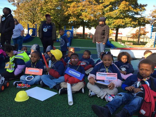 Students at Starms Early Childhood Center in Milwaukee gather for the unveiling of their new eco-friendly playground, which is designed to divert rainwater from local sewers and filter it before it reaches Lake Michigan. The children wear signs representing the kinds of jobs they learned about during the construction of the project.