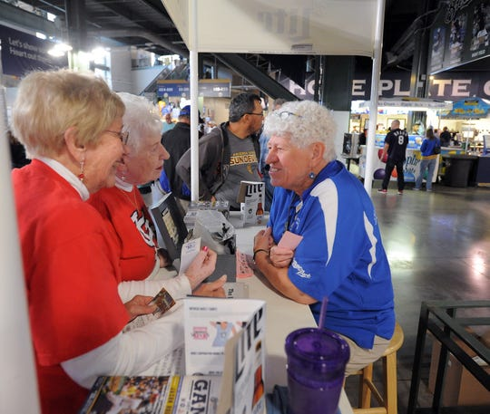 Phyllis Purdoff, right, the lady who hands out free soda vouchers at the Brewers Designated Driver booth before games, chats with a couple of fans before a 2015 Milwaukee Brewers game at Miller Park. After 31 years, Purdoff has retired.