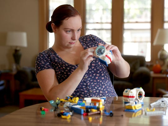 Autism rights advocate, Sarah Russell, works on legos to calm her nerves at her home in Wauwatosa.