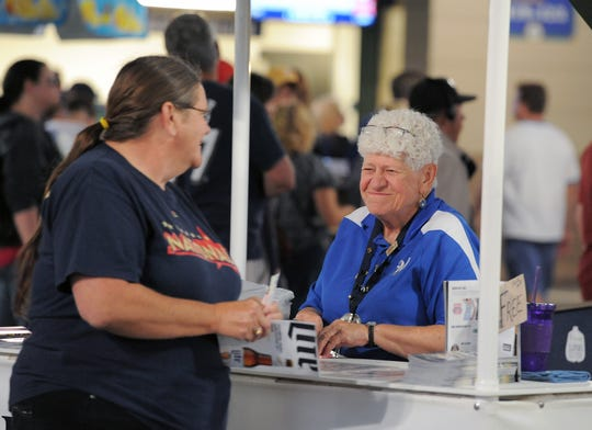Phyllis Purdoff, right, smiles at a woman who came to pick up a free soda voucher at the Miller Park Designated Driver booth before a game in 2015. Purdoff retired this month after 31 years of dispensing free sodas at Milwaukee Brewers games.