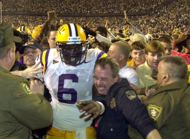LSU quarterback Rohan Davey (6) is helped from the field at the conclusion of the LSU-Auburn game in Baton Rouge, La. Saturday Dec. 1, 2001. LSU defeated Auburn 27-14. (AP Photo/Bill Haber)