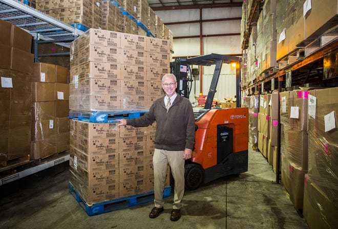 Tim Kean stands with a pallet of diapers stored in at the Second Harvest Food Bank facility on Old State Road 3. Second Harvest, which provides emergency food assistance, plans to also function as a diaper bank for organizations in need.