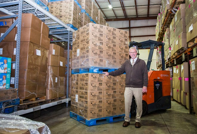 Tim Kean stands with a pallet of diapers stored in at the Second Harvest Food Bank facility on Old State Road 3.