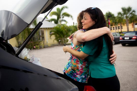 """Owner Susie Sayger, left, hugs Karen Tarpin, right, of Paychex, after loading dozens of bouquets into her car during a """"Petal it Forward"""" event at Heaven Scent Flowers in Bonita Springs on Wednesday, October 23, 2019. Tarpin is one of Heaven Scent's """"Petal it Forward"""" ambassadors, and will give away bouquets around the community."""