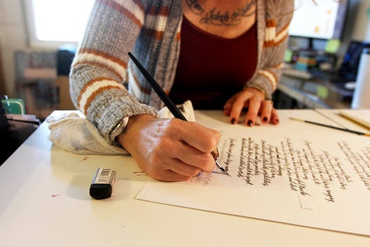 "Heather Spiegel of MoonBee Designs works on a recently commissioned calligraphy project. She became interested in hand lettering after realizing she needed ""something not on the computer,"" in light of her 20 years of work as a graphic designer."