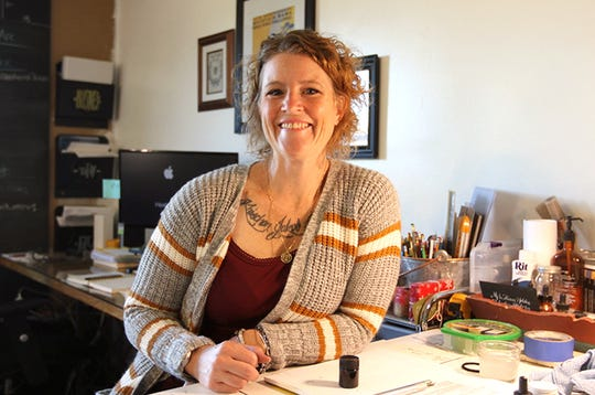 Heather Spiegel of MoonBee Designs sits at her desk in her home studio, where she works as a freelance graphic designer and takes on calligraphy commissions in her spare time.