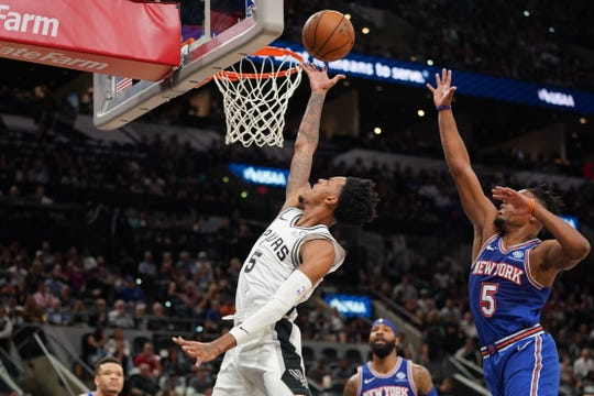 Oct 23, 2019; San Antonio, TX, USA; San Antonio Spurs guard Dejounte Murray (5) lays in a shot in front of New York Knicks guard Dennis Smith Jr. (5) during the first half at the AT&T Center.