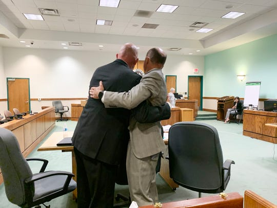 Former Luna County manager Ira Pearson, left, hugs his attorney Jess Lilley in Third Judicial District Court, Thursday, Oct. 24, 2019, after his charges were dropped during a jury trial.