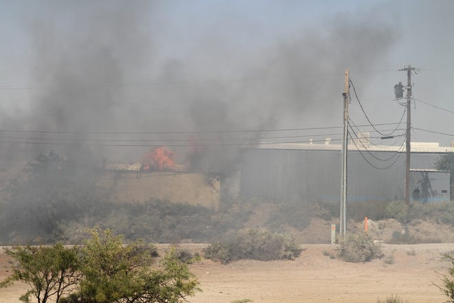Fire engulfs the warehouse behind National Furniture Liquidators on Thursday, Oct. 24.