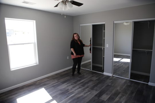 Tres Rios Habitat for Humanity spokesperson Hope Tyler shows off the mirror-adorned closet doors in one of the bedrooms of the new Crouch Mesa home her organization has built.