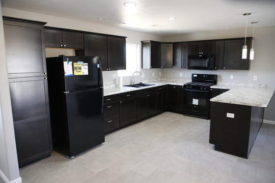 The new home features a spacious kitchen with a large pantry, bar, decorative and recessed lighting, and new appliances.