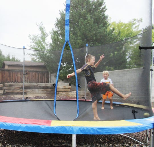 Brothers Ryker (left) and Axel Burns play on a trampoline at the family's Farmington home. Four years after his Type-1 diabetes diagnosis, 7-year-old Ryker takes an active part in staying healthy.
