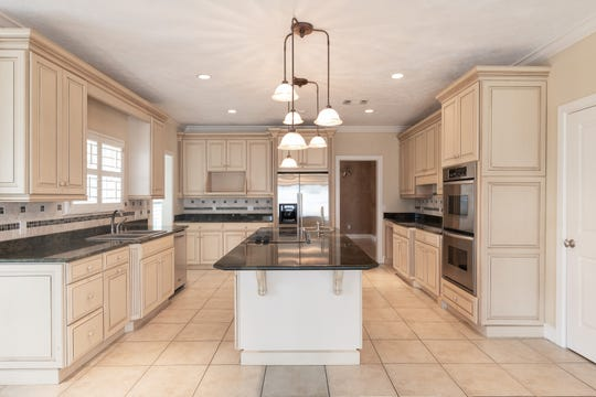 The kitchen features a large island and stainless appliances.