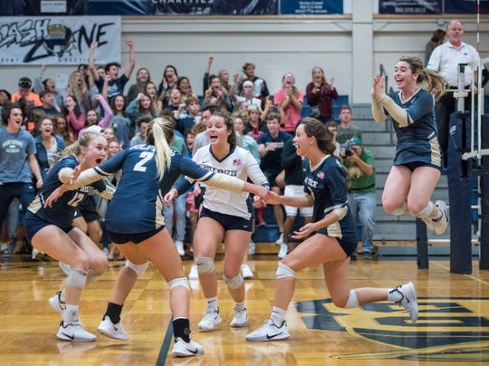 The Dolphins celebrate their victory during the Middleburg vs Gulf Breeze FHSAA Class 5A first round volleyball tournament match at Gulf Breeze High School on Wednesday, Oct. 23, 2019.
