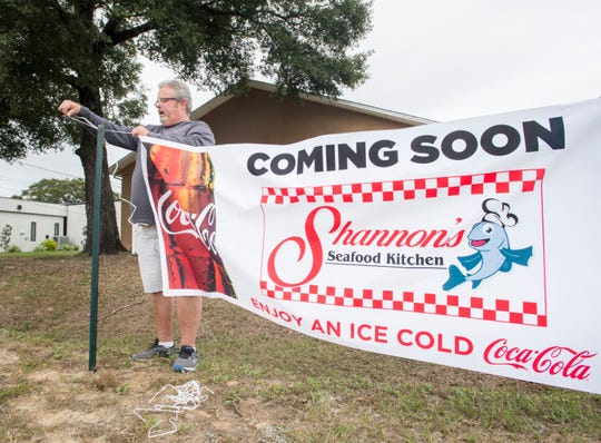 Owner Shannon Kersey hangs a banner Thursday announcing the soon-to-open Shannon's Seafood Kitchen restaurant on Pine Forest Road on Thursday.