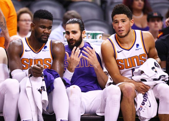 Phoenix Suns guard Ricky Rubio (center) talks to center Deandre Ayton and guard Devin Booker against Sacramento Kings in the second half on Oct. 23, 2019 in Phoenix, Ariz.