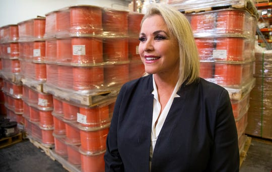 Former television news anchor Jineane Ford, who now works as the chief information officer for PCT International Inc., walks through the plant in Mesa on Oct. 23, 2019.