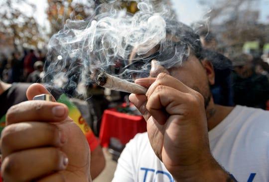 Un activista enciende un cigarro de marihuana durante una protesta.