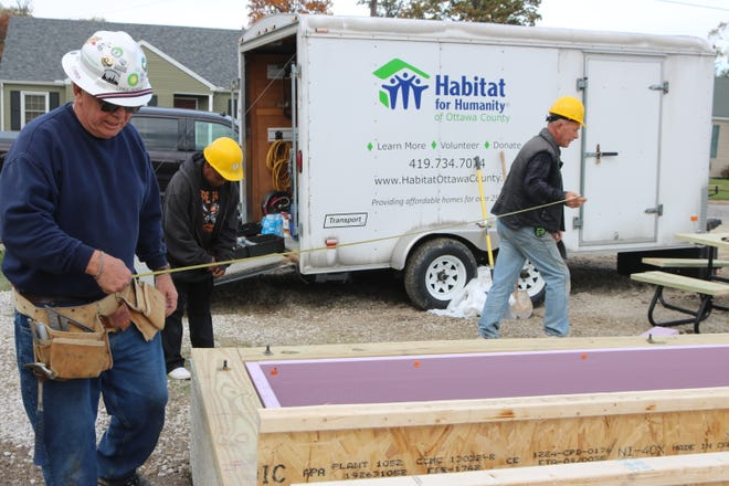 Volunteers Paul Henry, Ann Rogers and Don Kiser, with Habitat for Humanity of Ottawa County, take a measurement as work continues on the home being built for the Stockmaster family at 129 Walnut Street in Port Clinton.