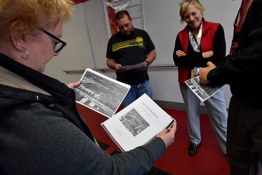 "1969 grad Debbie Myers, left, looks at a current photo of Dover High School, left, and one from 1954 as the school looked when she attended. The community was invited to take a walk down ""Memory Lane"" in the current school as the district prepares to move classes to the newly constructed high school for the 2020 school year. Thursday, October 24, 2019. John A. Pavoncello photo"