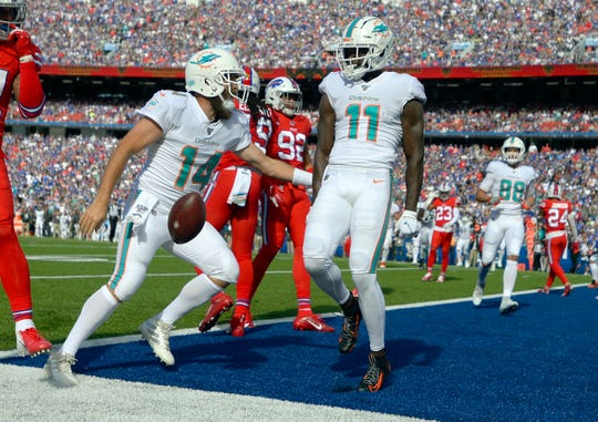 Miami Dolphins quarterback Ryan Fitzpatrick, left, celebrates his touchdown pass to wide receiver DeVante Parker, right, in the first half of an NFL football game against the Buffalo Bills. Parker, a 2015 first-round pick, could be the next move in winless Miami's fire sale and would give Bills an upgrade to overall receiver corps.