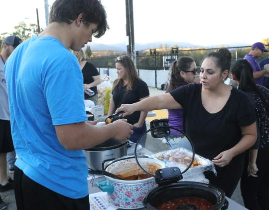 Mary Ann Cruz serves up her Tex Mex style chili with cornbread to Shasta High junior varsity football player William McMacken after practice on Wednesday, Oct. 23, 2019. The chili meal is part of a pre-River Bowl tradition at Shasta.